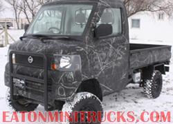Black camo mini truck with push bumper and lift in the snow