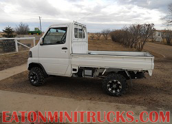 mini truck with snow plow and snow tracks