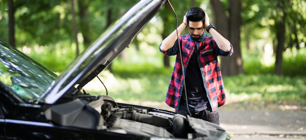 man-standing-next-to-broken-down-car