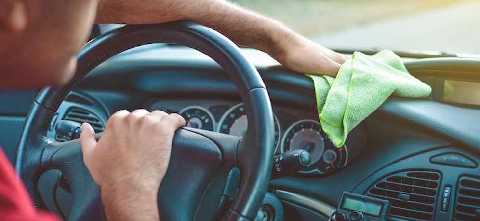 man wiping down interior dashboard