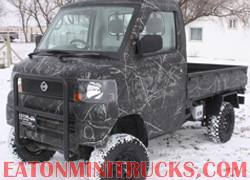 Black camo mini truck with push bumper and lift in the snow